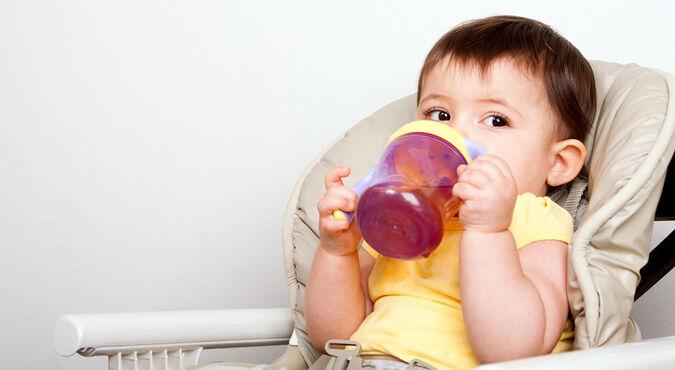 Criança sorridente de maria-chiquinha segurando o copo de treinemento