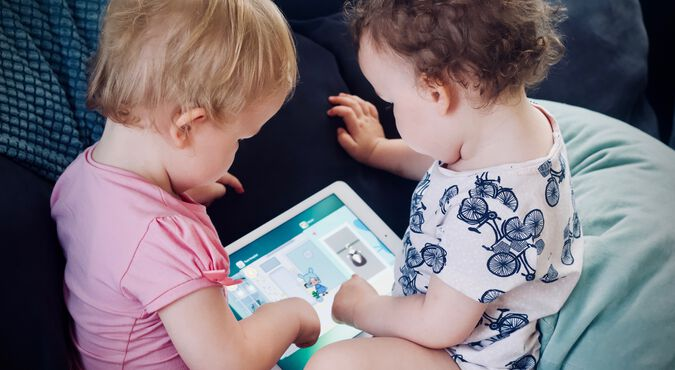 Criança e bebê à frente de um tablet com a supervisão da mamãe