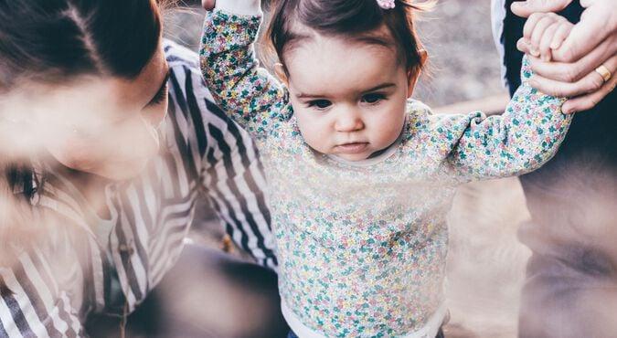 Bebê caminhando de mãos dadas com papai e mamãe