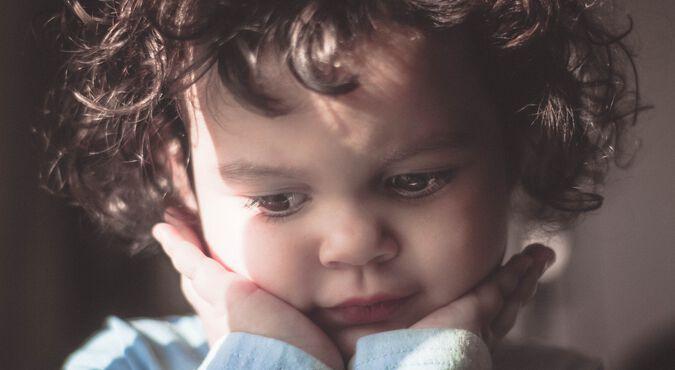 Criança com as maõs no rosto demonstra excesso de timidez na infância