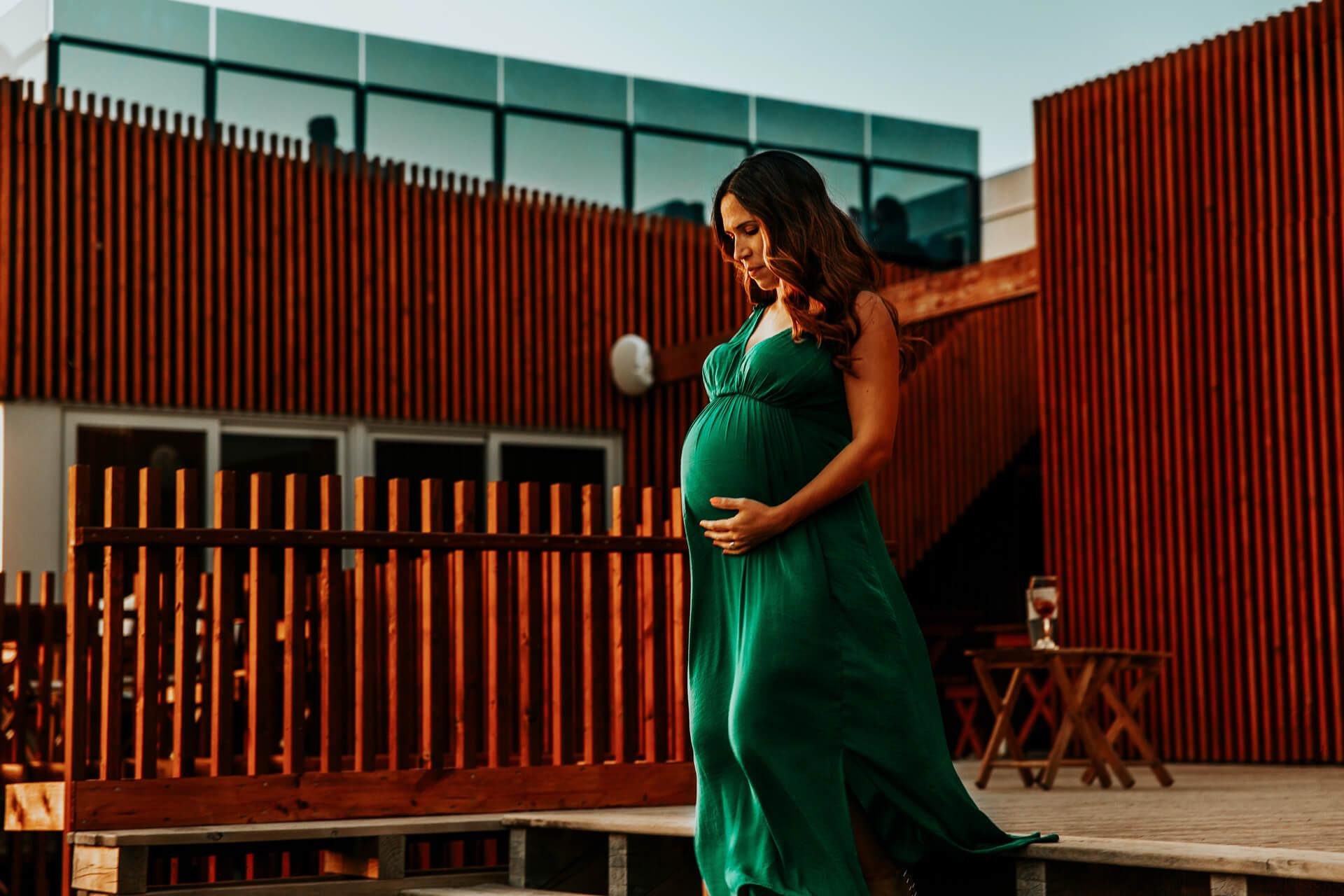 Mulher em pé na frente de um prédio  Descrição gerada automaticamente